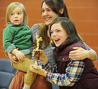 NWA Media/ANDY SHUPE - Aiden Kelly, 10, a fifth-grader at Washington Elementary School in Fayetteville, right, reacts to winning the school's annual spelling bee Friday, Dec. 19, 2014, alongside his mother, Jeananne Kelly, and 3-year-old brother, Cooper, in the school's gymnasium. Aiden will represent the school in the county spelling bee in January.
