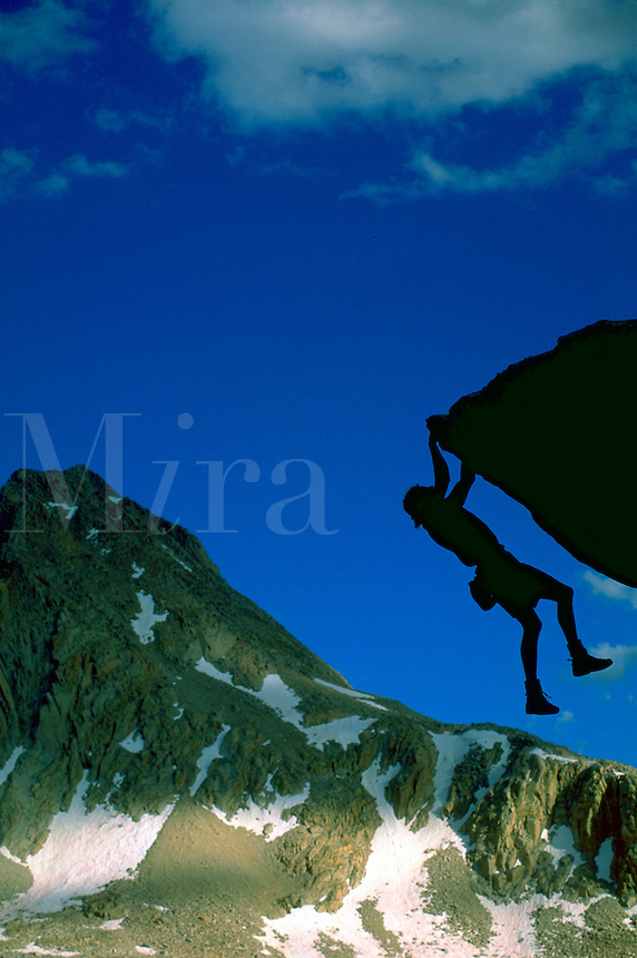 Silhouette of a climber hanging on precariously by two hands to a rocky outcropping beneath Mount Hexley in the Evolution Peaks region in Kings Canyon National Park, California with blue sky in the background.<br />