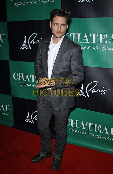 Peter Facinelli.Peter Facinelli on the red carpet at Chateau Nightclub inside Paris Las Vegas, Las Vegas, Nevada, USA..January 28th, 2012.full length grey gray suit jacket jeans denim white top hands stubble facial hair.CAP/ADM/MJT.© MJT/AdMedia/Capital Pictures.