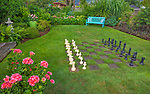 Vashon-Maury Island, WA: Oversized chess board in a lawn with bright blue bench in a cottage garden featuring bright pink geraniums, ferns and hydrangeas
