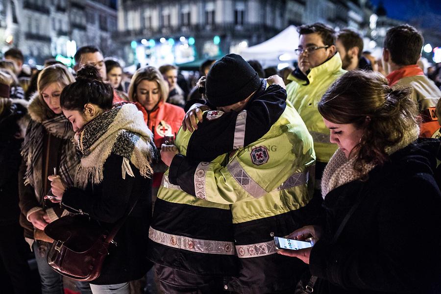 BRUXELLES,Belgique: Des membres de la Croix Rouge s'enlacent devant la Bourse. Plus de 200 secouristes de la Croix-Rouge ont pris part au rassemblement à la Bourse de Bruxelles ce vendredi 25 mars 2016.