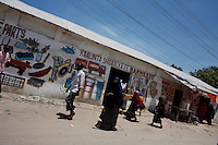 """Somalis shop along  a center street In  Somalia's war torn capital Mogadishu on Tuesday April 22nd 2008.///..Sporadic street fighting between Ethiopian troops and Islamic fighters trying to bring down Somalia's shaky .government has killed 81 people on April 19 and 20, the head of a .local human rights group said Sunday. .""""The casualties ... were caused by Ethiopians using heavy artillery and .tank shells in residential areas of the war-torn capital. We condemn .this latest fighting,"""" said Sudan Ali Ahmed, chairman of Elman Human .Rights. Besides the 81 dead, 119 people had been wounded, he said. .Reports on Monday April 21 say Ethiopian troops have taken control of a mosque with a large .number of civilians inside following heavy fighting with insurgents. .The reports say a number of civilians were killed inside the mosque and others are being held by Ethiopians against .their will. .This apparent increase in the brutality of attacks may be caused partly by a .recent American decision to classify the Shabab (youth), the Islamic Courts .Union's former military wing, as a terrorist group. Battered by Ethiopian attacks .and by infighting between sub-clans engaged in the insurgency, Shabab .fighters now probably number fewer than 400. But America's decision to .demonise them has boosted jihadist commanders such as Aden Hashi Ayro, .strengthening his reputation for piety and anti-Americanism, which has itself .been boosted by recent missile attacks that have accidentally killed civilians...Philippe Lazzarini, head of the UN Office for the Coordination of Humanitarian Affai .rs (OCHA) Somalia, said on Monday April 21st that the combination of a severe drought, civil insecurity and h .yperinflation was pushing the country to the brink. If the situation were happening a .nywhere else """"it would have triggered outrage"""". .Lazzarini said Somalia was """"on the eve of a massive, massive humanitarian catast .rophe"""", with an estimated 2.5 million people needing assistance. .""""If thin"""