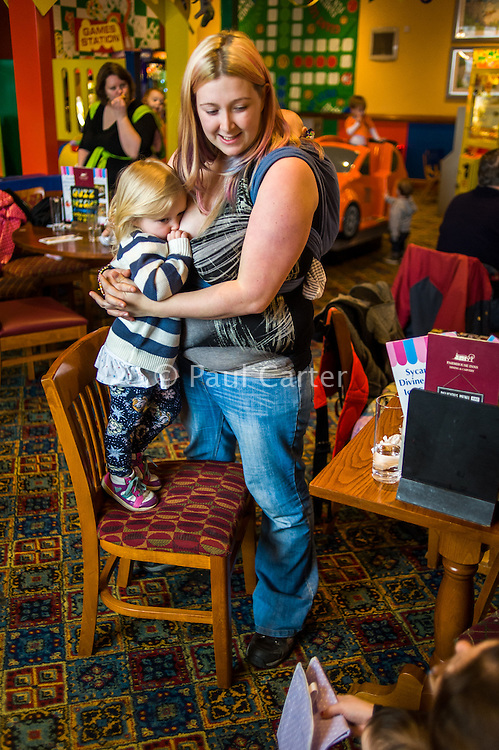 A mother breastfeeds her two year old daughter with her twelve week old baby asleep in a sling on her back.in the family restaurant and play area of a pub. The mother is standing and the boy is feeding while standing on a chair.<br /> <br /> Lancashire, England, UK<br /> <br /> Date Taken:<br /> 07-01-2015<br /> <br /> © Paul Carter / wdiip.co.uk