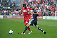 New England defender Chris Tierney (8) impedes Chicago forward Patrick Nyarko (14).  The Chicago Fire defeated the New England Revolution 3-2 at Toyota Park in Bridgeview, IL on Sept. 25, 2011.