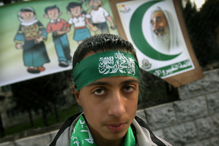 A kid supporter of Hamas outside a polling station, at the West Bank city of Ramallah, during election day for the Palestinian parliament. Sheikh Ahmed Yassin, spiritual leader of Hamas killed by Israel on 2005, is on poster behind.