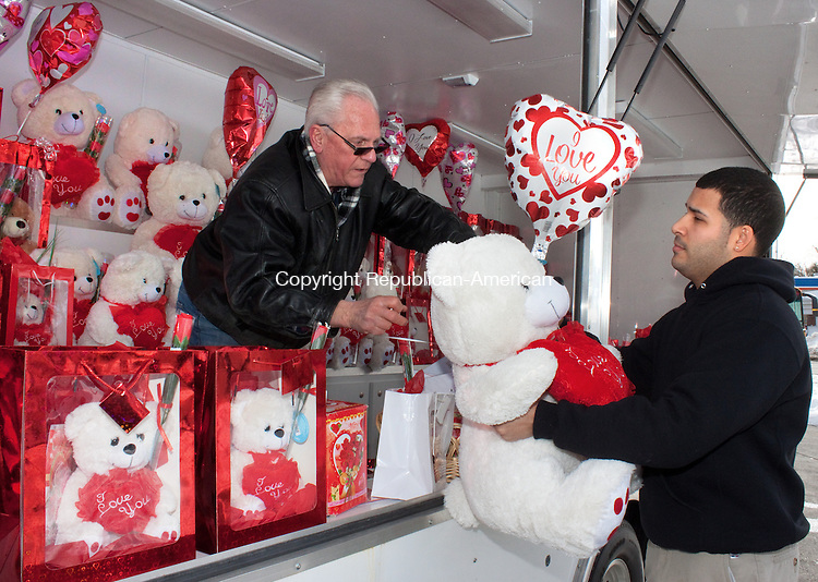WATERBURY CT- FEBRUARY 12 2014 021214DA01- Angel Carrasquillo of Naugatuck buys his girlfriend a white teddy bear for Valentines Day Wednesday from Bob Fantaine who owns the concession trailer on the corner of Wolcott St and Stillson Rd. in Waterbury. Fantaine who is the owner of Robert's Enterprise has been selling holiday gifts on Wolcott St. for over 40 years.