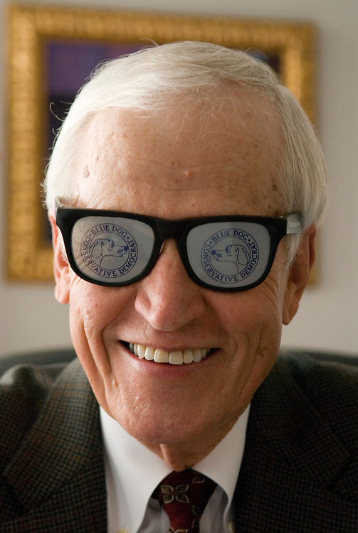 Former Congressman Charlie Stenholm, D-Texas, puts on his Blue Dog Democrat sunglasses in his office at the Olsson, Frank and Weeda law firm in Washington on Friday, Nov. 17, 2006.