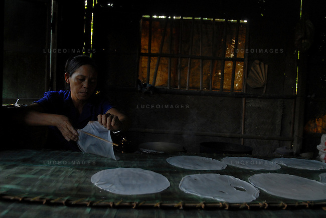 A Vietnamese woman makes rice paper in her home in Hoi An, Vietnam.