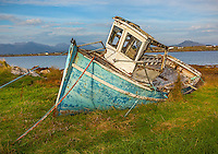 County Galway, Ireland: Weathered blue fishing boat near the shoreline of Bertraghboy Bay in the village of Roundstone with Connemara Mountains in the distance