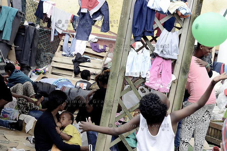 Roma, 13 Giugno 2015<br /> Via Tiburtina.<br /> Centinaia di migranti hanno trovato rifugio nel centro di accoglienza Baobab di Via Cupa e nelle vie limitrofe.<br /> Uomini e donne nel cortile.<br /> Mamma allatta il figlio