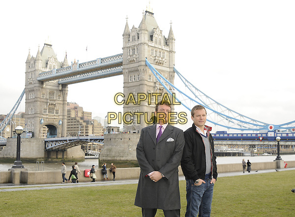 "SHANE RICHIE & LEX SHRAPNEL  .The ""Minder"" 80's sitcom remake photocall, Potters Field, London, England..January 13th, 2009.half 3/4 length grey gray coat jacket purple jacket black check checked top jeans denim hands in pockets tower bridge tie.CAP/CAN.©Can Nguyen/Capital Pictures."
