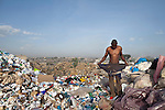 13 february 2013 - Dandora dumpsite, Nairobi, Kenya - A Kenyan man puts on some clothes before starting to search for items to sell and food waste to eat at the Dandora dumpsite, one of the largest and most toxic in Africa. Located near slums in the east of the Kenyan capital Nairobi, the open dump site was created in 1975 and covers 30 acres. The site receives 2,000 tonnes of unfiltered garbage daily, including hazardous chemical and hospital wastes. It is a source of survival for many people living in the surrounding slums, however it also harms children and adults' health in the area and pollutes the Kenyan capital. Photo credit: Benedicte Desrus