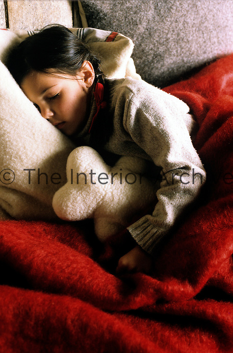 A little girl lies asleep clutching her teddy bear nestled amongst soft cushions and blankets