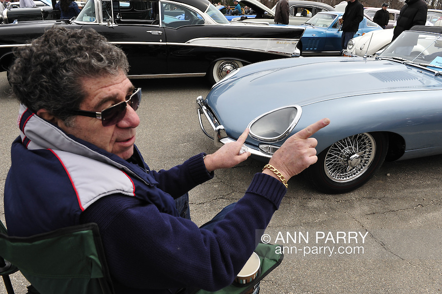 BERNIE HOFFMAN is pointing to his 1967 E Type Jaguar 4.2 Series 1 as he explains it was the last year for a long time that headlights covered with glass were legal, at  the 58th Annual Easter Sunday Vintage Car Parade and Show sponsored by the Garden City Chamber of Commerce. Hundreds of authentic old motorcars, 1898-1988, including antiques, classic, and special interest participated in the parade.