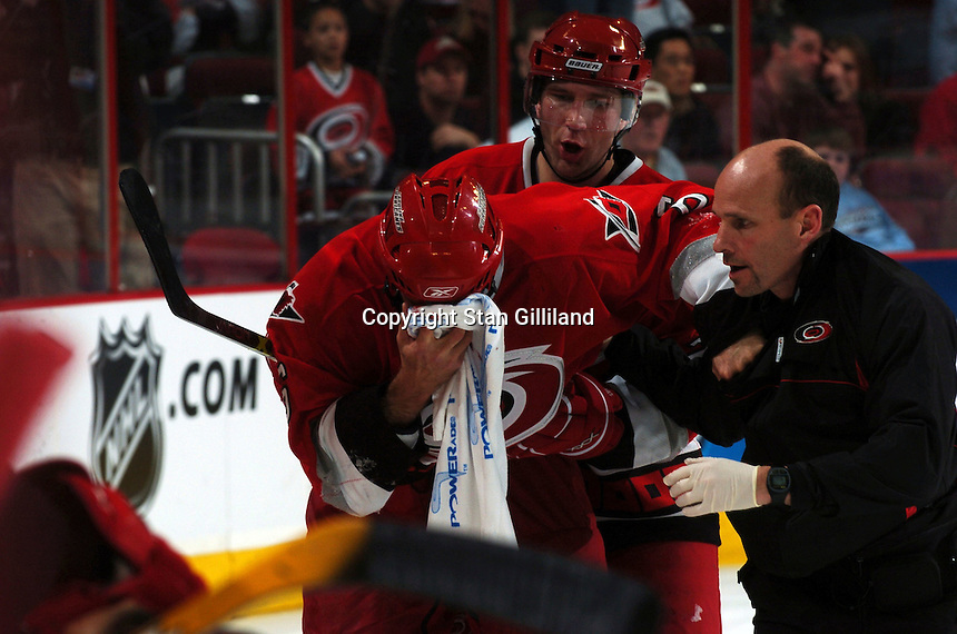 Carolina Hurricanes' defenseman Bret Hedican holds a towel to his face after taking a high stick during a game with the Nashville Predators Friday, January 13, 2006 in Raleigh, NC. Following is teammate Erik Cole. Carolina won 5-4 after a shootout.