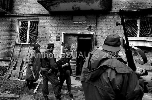Grozny, Chechyna.1995.A resident of an apartment complex points to show Russian ministry troops where a Chechen sniper hide out is thought to be.