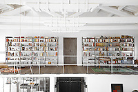 One end of the mezzanine walkway which runs around the perimeter of the space is occupied by a pair of industrial style bookshelves