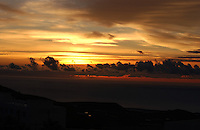 Sun breaking through clouds with silhouetted coastline in the foreground, San Miguel, Tenerife, Canary Islands