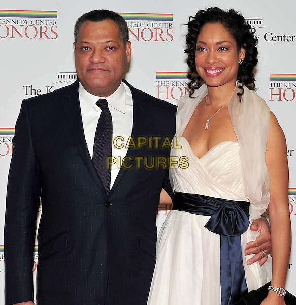 Laurence Fishburne & Gina Torres .The formal Artist's Dinner at the United States Department of State in Washington, D.C., USA..December 4th, 2010.half length black dress suit white tulle blue sash waist married husband wife .CAP/ADM/RS.©Ron Sachs/CNP/AdMedia/Capital Pictures.