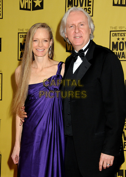 SUZY AMIS & JAMES CAMERON .15th Annual Critics' Choice Movie Awards - Arrivals held at the Hollywood Palladium, Hollywood, California, USA, 15th January 2010..half length purple dress one shoulder black bow tie tuxedo tux married couple husband wife .CAP/ADM/BP.©Byron Purvis/Admedia/Capital Pictures