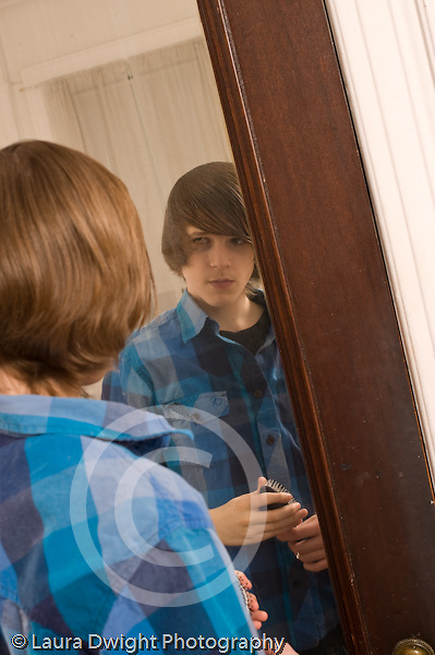 Teenage boy looking at self in mirror Caucasian vertical age 14