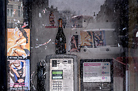 UK. London. 29th March 2018<br /> A bottle of champagne and prostitutes calling cards in a phone booth in central London.<br /> Andrew Testa for the New York Times