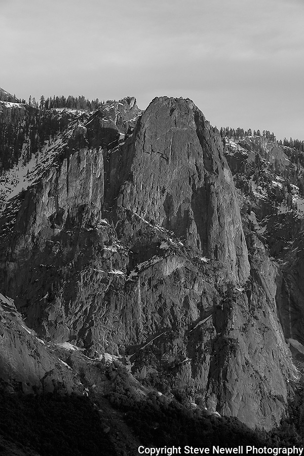 """Sentinel's Sunset"" Black and White vertical Yosemite National Park. Sentinel Rock formation located in Yosemite National Park near the Four Mile Trailhead across the valley floor from the big Yosemite Falls Waterfall.  The large monolithic rock formations in Yosemite provide some of the best rock climbing and trail hiking in the world.  At sunset every single rock formation in the park changes colors as the day goes by and light up at every sunset.  The colors of the granite walls are quite spectacular and a must visit for everyone in the world to see in person."