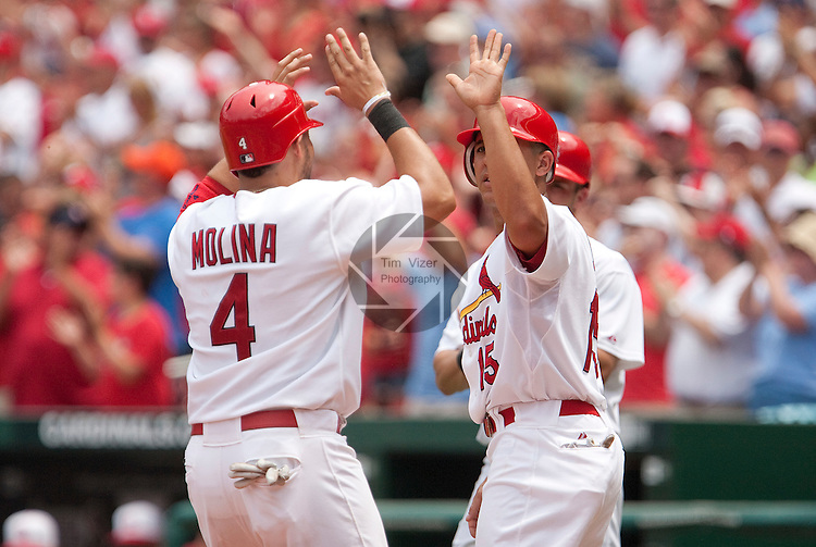 July 4, 2010          St. Louis Cardinals catcher Yadier Molina (4) crosses home plate and gives high-fives to St. Louis Cardinals left fielder Jon Jay (15) in the third inning.  Hidden behind Jay is St. Louis Cardinals second baseman Skip Schumaker, who also scored with the other two after St. Louis Cardinals starting pitcher Adam Wainwright doubled to right centerfield.  Cardinals players Wainwright, Molina, Albert Pujols, Chris Carpenter, and Matt Holliday were all selected to play in the All-Star Game.  The St. Louis Cardinals defeated the Milwaukee Brewers 7-1 in the final game of a four-game homestand at Busch Stadium in downtown St. Louis, MO on Sunday July 4, 2010.