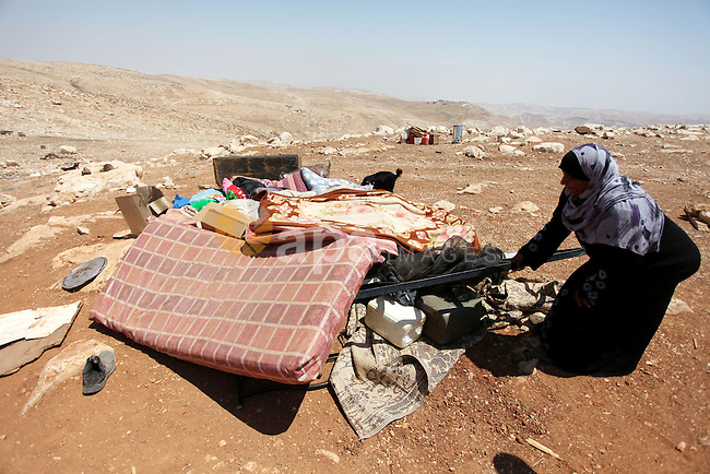 A Palestinian Bedouin woman searches in the rubble of her damaged tent after it was dismantled by Israeli bulldozers under the pretext of building without permits at al-Baq'a camp near the West Bank city of Jericho, Aug 20, 2013. Photo by Issam Rimawi
