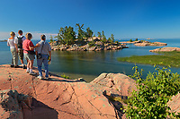 tourists look onwaards from Chikanishing River as it joins Collins Inlet at Georgian Bay. Killarney Provincial Park. Ontario. Canada<br />