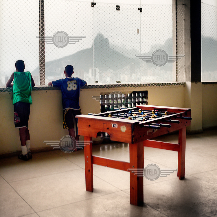 Two boys, from Cant Agalo Favela, stare out of the window of a community social centre towards Pão de Açúcar (Sugar Loaf Mountain).