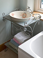 A contemporary wrought-iron washstand in the bathroom incorporates a Victorian wash basin