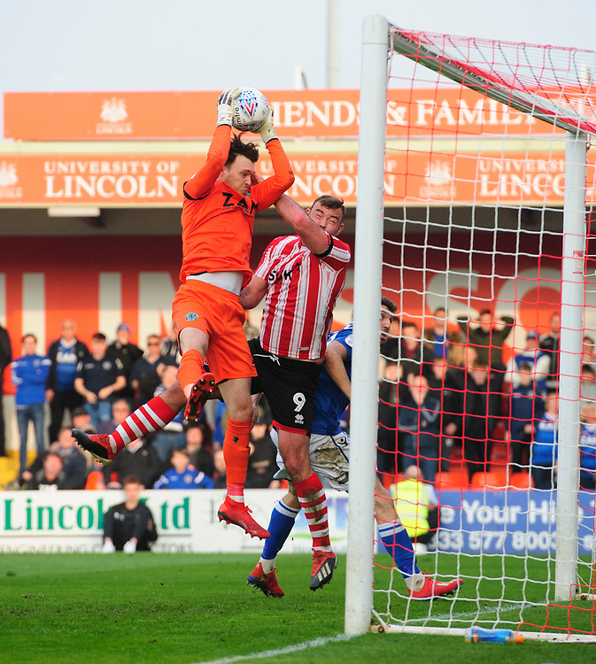 Macclesfield Town's Kieran O'Hara claims a high ball under pressure from Lincoln City's Matt Rhead<br /> <br /> Photographer Chris Vaughan/CameraSport<br /> <br /> The EFL Sky Bet League Two - Lincoln City v Macclesfield Town - Saturday 30th March 2019 - Sincil Bank - Lincoln<br /> <br /> World Copyright © 2019 CameraSport. All rights reserved. 43 Linden Ave. Countesthorpe. Leicester. England. LE8 5PG - Tel: +44 (0) 116 277 4147 - admin@camerasport.com - www.camerasport.com