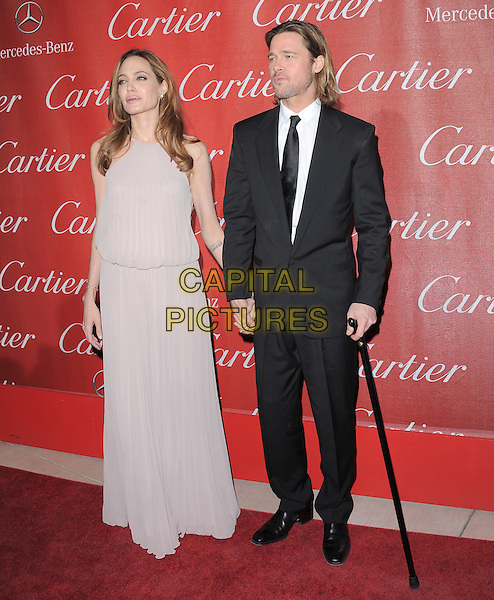 Angelina Jolie & Brad Pitt .attending the 2012 Palm Springs International Film Festival Awards Gala held at The Palm Springs Convention Center in Palm Springs, California, USA, January 7th 2012. .arrivals full length beige greige dress long maxi holdings hands halterneck crutch walking stick cane  black suit tie couple brangelina angie grey gray .CAP/RKE/DVS.©DVS/RockinExposures/Capital Pictures.