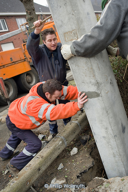 Workers employed by a publicly owned electricity company replace a pylon in the city of Liege, Belgium.