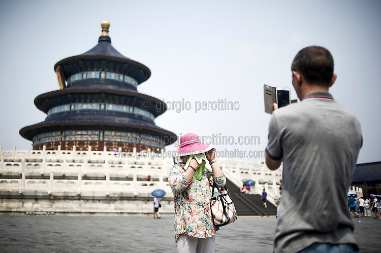 A Chinese man takes a picture to her wife as she dries her face from sweat due to the Summer heat on the pavillion of Tian Tan the Temple of Heaven in Beijing, China, July 20, 2014.<br /> <br /> Smartphones are an essential tool of Chinese ordinary life. Everywhere in China, people use them to take pictures to share online, to talk and chat, to play videogames, to get access to the mainstream information, to get connected one each other. In the country where the main global social media are forbidden - Facebook, Twitter and Youtube are not available  -, local social networks such as WeChat have a wide spread all over the citizens. The effect is an ordinary and apparently compulsive way to get easy access to digital technology and modern way of communication. <br /> A life through the display. Yes, We Chat.<br /> <br /> © Giorgio Perottino