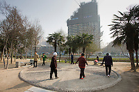 People walk in a circle as part of their morning exercise in the park by the City Wall of Xian, China