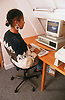 Woman sitting at desk using computer during Adult education class,