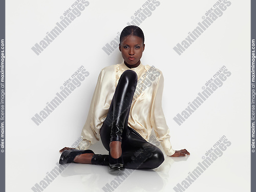 Young woman fashion model sitting on a studio floor