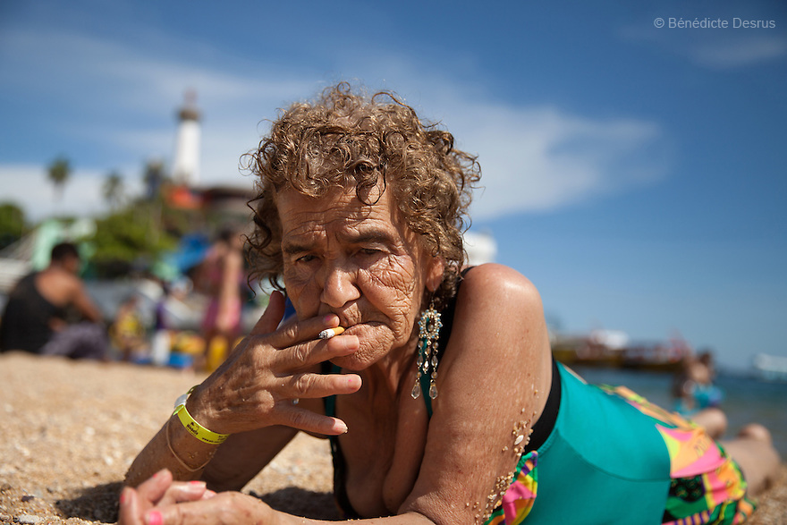 Victoria, a resident of Casa Xochiquetzal, smokes a cigarette at the beach during a trip organised by the shelter in Acapulco, Mexico on September 7, 2013. Casa Xochiquetzal is a shelter for elderly sex workers in Mexico City. It gives the women refuge, food, health services and a space to learn about their human rights, as well as courses to help them rediscover their self-confidence and deal with traumatic aspects of their lives. Casa Xochiquetzal provides a space to age with dignity for a group of vulnerable women who are often invisible to society at large. It is the only such shelter existing in Latin America. Photo by Bénédicte Desrus