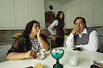 Kai and Katinka Palm with their daughter, in their kitchen. She does not wear Roma clothes, but he is more traditional wearing a longsleeve shirt. Finnish Roma would never bare their torso to outsiders, they would frown upon Romanies showing their tattoos. Tempere, Finland 2005