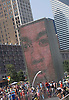 July 16, 2005: On a hot summer day, visitors to Millennium Park in Chicago take in the Crown Fountain.  Faces of Chicagoans are displayed through video on the two large glass block towers, and water is sprayed from the figures mouths and the top of the fountain. Photo by Kevin J. Miyazaki/Redux for The New York Times