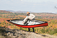 A solo canoeist lifts his canoe to portage carry it while standing on top of a hill with fall color visible.