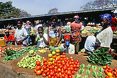 Chisimba Falls, Zambia. Market scene; men and women selling fresh vegetables; okra, tomatoes, onions, etc.