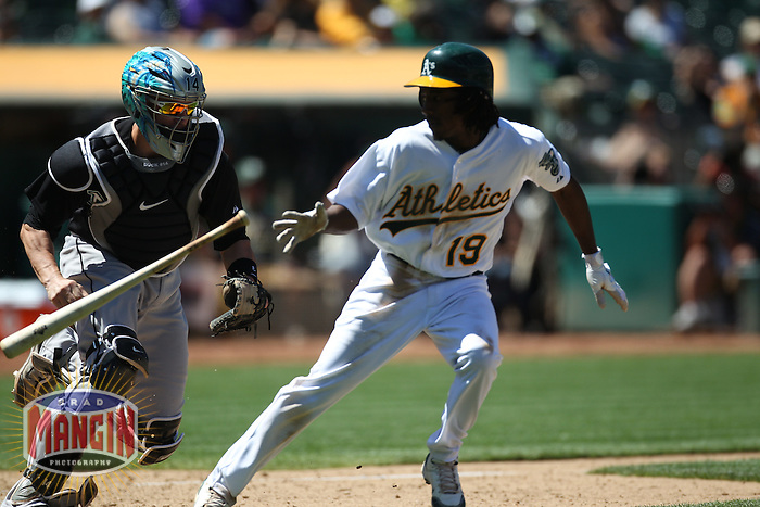OAKLAND, CA - JUNE 30:  John Buck #14 of the Florida Marlins chases Oakland Athletics batter Jemile Weeks #19 up the first base line trying to tag him after Weeks struck out during the game at the Oakland-Alameda County Coliseum on June 30, 2011 in Oakland, California. Photo by Brad Mangin
