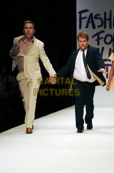 DAVID WALLIAMS & JAMES CORDEN.The Fashion For Relief Haiti 2010 show for London Fashion Week Autumn/Winter 2010 at Somerset House, London, England..February 18th, 2010.LFW catwalk runway full length black beige suit walking holding hands pink shirt white funny .CAP/CAS.©Bob Cass/Capital Pictures.