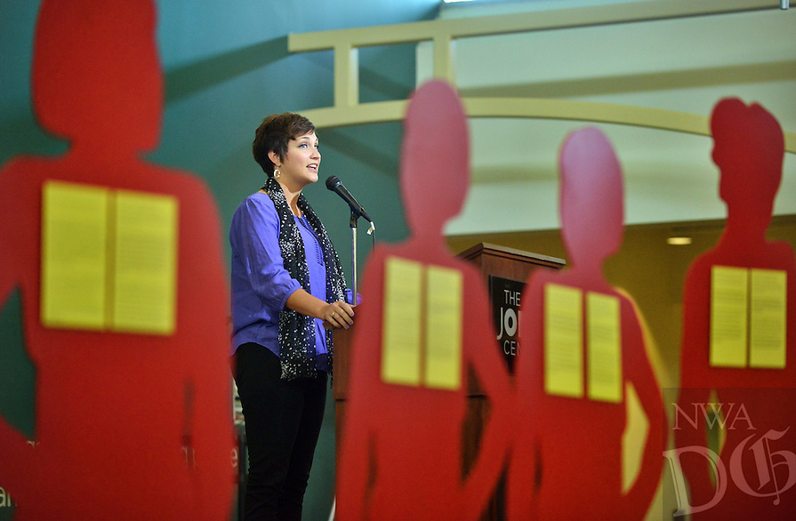STAFF PHOTO BEN GOFF  @NWABenGoff -- 10/04/14 Elizabeth Baker, a survivor of domestic violence, speaks during Peace at Home Family Shelter's Domestic Violence Awareness Month Kickoff event at the Jones Center in Springdale on Saturday October 4, 2015. The 'silent witnesses' silhouettes represent the 18 victims of domestic partner or family homicide in Arkansas in 2013.