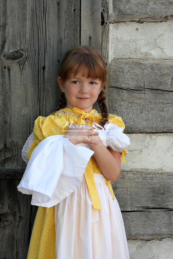A young girl walking through grass in American with a doll historical clothing