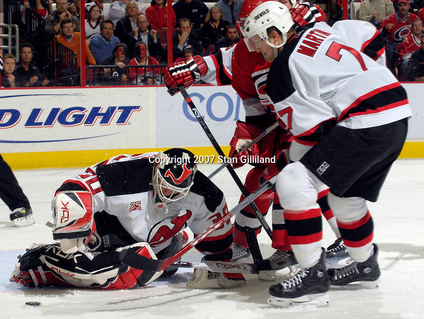 New Jersey Devils' goalie Martin Brodeur makes a save as teammate Paul Martin (7) holds off the Carolina Hurricanes at the crease Thursday, March 15, 2007 at the RBC Center in Raleigh, NC. New Jersey won 3-2.