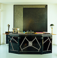 The large black-lacquer desk was designed by Jeanne Lanvin in the 1930s; its arrangement in front of a large  abstract painting in tones of grey and black cleverly implies a self-contained office space